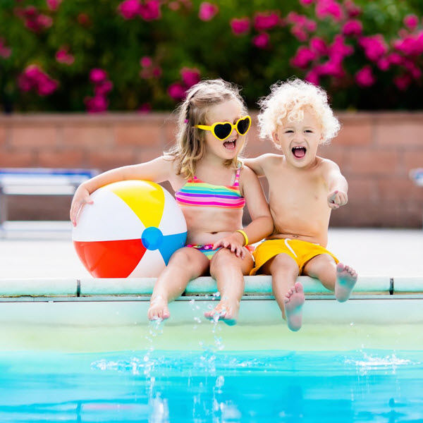 2 children sitting on the side of a swimming pool with a beach ball